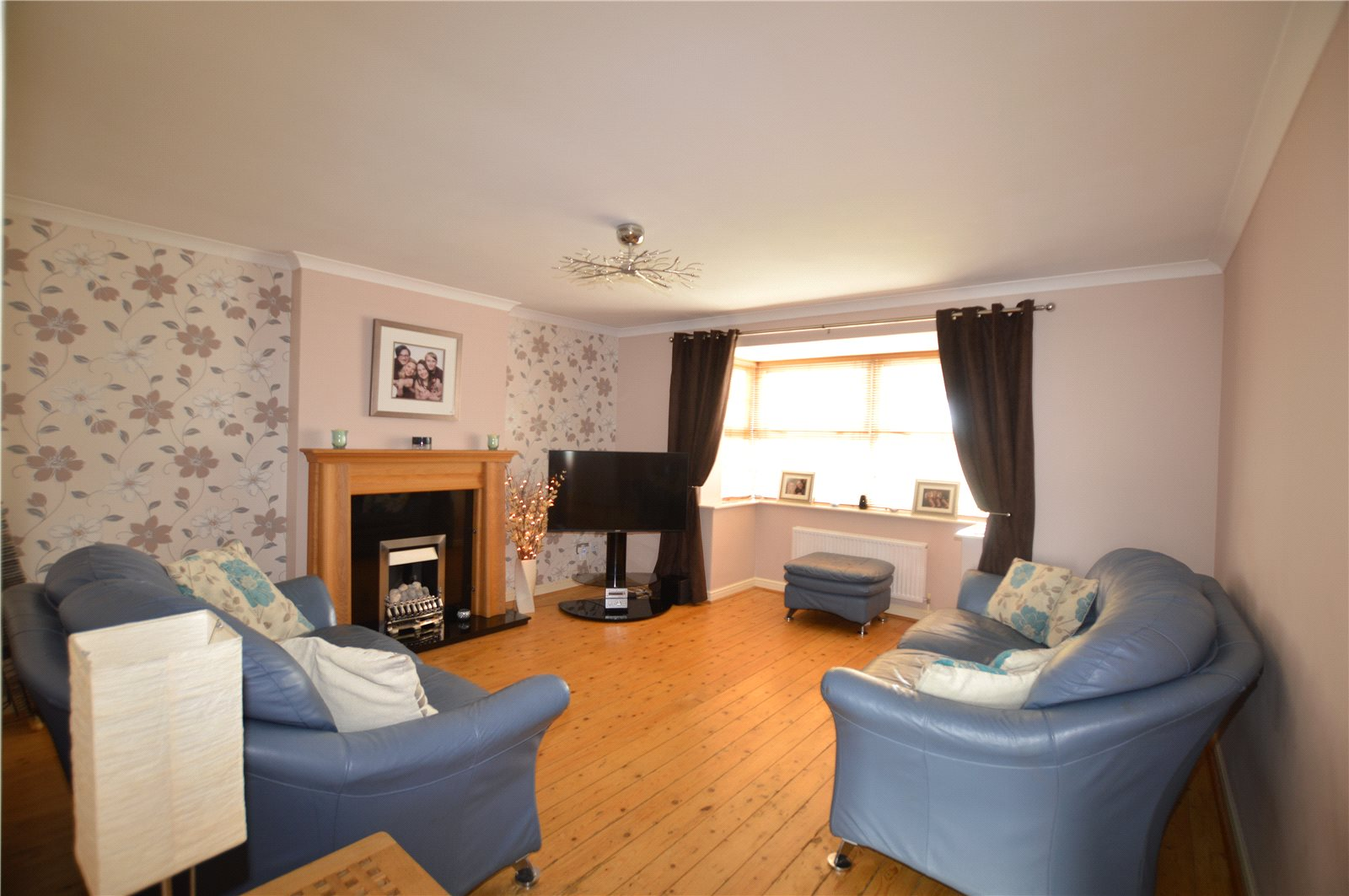 Property for sale in Morley, living area, blue sofas and printed wallpaper